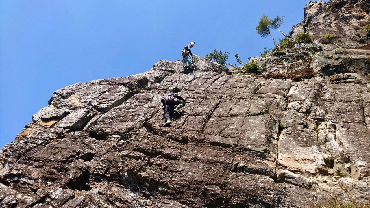 上部にてビレイ(安全確保)を行う代表山本と登りこむ田嶋